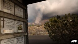The smoking lava flow from the Cumbre Vieja volcano is seen from the cemetery of the neighborhood of Todoque in Los Llanos de Aridane on the Canary island of La Palma in Sept. 24, 2021.