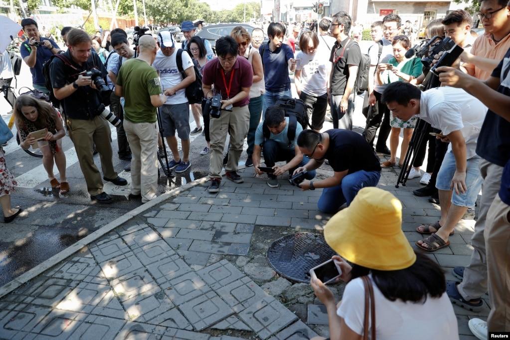 記者2018年7月26日在北京的美國大使館外爆炸現場拍照。 在社交媒體上發布的視頻顯示煙霧在大使館半平方公里範圍內繚繞。 至少有兩名在場者表示他們在爆炸時感受到了震動。 儘管這次爆炸規模很小,但還是吸引了國際目光,因為中國政府向來在位於北京的大使館地區施行嚴格的安保,這種針對高級場所的攻擊非常稀少。