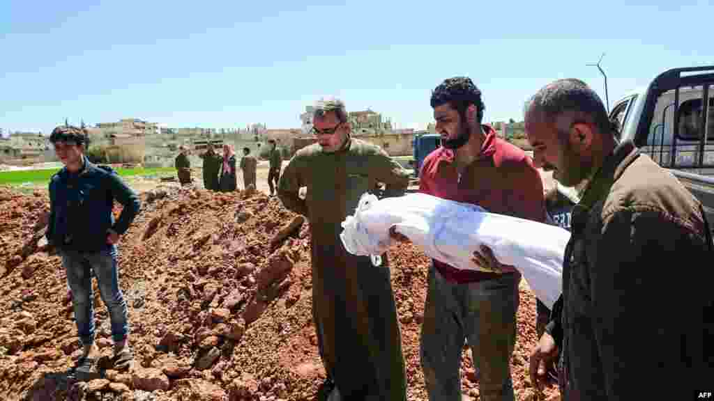 Syrians bury the bodies of victims of a a suspected toxic gas attack in Khan Sheikhun, April 5, 2017.