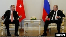 Turkish President Recep Tayyip Erdogan speaks to Russian President Vladimir Putin (R) during their meeting in St. Petersburg, Russia, August 9, 2016.