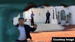 남아프리카공화국 프리토리아 주재 북한대사관에서 북한 외교관들이 취재진을 저지하고 있다. 사진제공=줄리안 로드마이어 기자