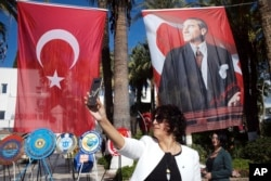 Photo taken on Oct. 28, 2018 shows a Turkish womPhoto taken on Oct. 28, 2018 shows a Turkish woman taking a selfie in front of a poster of Mustafa Kemal Ataturk, Turkey's founder, in Bodrum, Turkey, a day before thousands of army officers, soldiers, teachers, politicians, including Turkey's President Recep Tayyip Erdogan visit his mausoleum on Republic Day in Ankara.