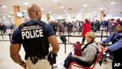 Petugas keamanan mengawasi penumpang di bandara Hartsfield–Jackson, Atlanta (foto: dok). Bandara ini menjadi bandara tersibuk di dunia dengan melayani 100 juta lebih penumpang dalam setahun.