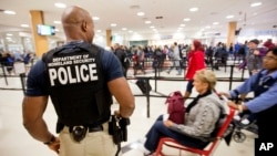 A Department of Homeland Security police officer stands at a security checkpoint at Hartsfield–Jackson Atlanta International Airport, Nov. 25, 2015.