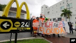 People protest for increased minimum wages outside a McDonald's restaurant in the Little Havana area in Miami, Florida.