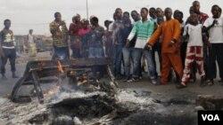 Pendukung presiden Alassane Ouattara menunjuk mayat yang terbakar yang diyakini sebagai pendukung Laurent Gbagbo, di Distrik Abobo, Abidjan (7/3).