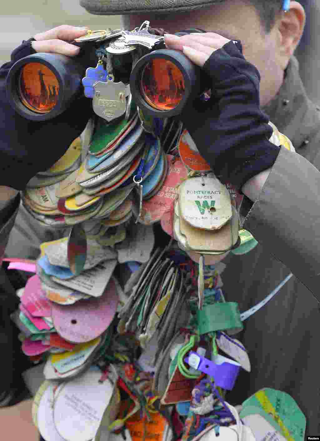 A racegoer looks through his binoculars covered with race passes at the Cheltenham Festival horse racing meet in Gloucestershire, western England. The four-day Cheltenham Festival is a highlight of the annual jump racing calendar.