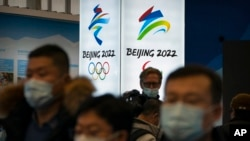 2021年2月5日,在北京郊區延慶冬奧會場館遊客中心,戴著口罩的觀眾觀看展覽。