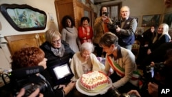 Verbania's Mayor Silvia Marchionini, right, presents Emma Morano with a cake during a celebration of her 117th birthday in Verbania, Italy, Tuesday, Nov. 29, 2016.
