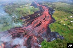 In this Saturday, May 19, 2018, photo released by the U.S. Geological Survey, lava flows from fissures near Pahoa, Hawaii.