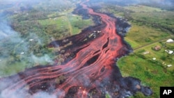 FILE - In this May 19, 2018, photo released by the U.S. Geological Survey, lava flows from fissures near Pahoa, Hawaii.