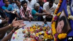 Para pendukung mantan pejabat tertinggi negara bagian Tamil Nadu, Jayaram Jayalalithaa, memberikan penghormatan terakhir bagi almarhum di depan foto yang diletakkan di depan kantornya di Mumbai, India (6/12).