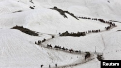 Hindu pilgrims cross a snow-covered mountain to reach the Amarnath cave shrine where they worship an ice stalagmite that Hindus believe to be the symbol of Lord Shiva, at Waval in the Kashmir region, July 6, 2019.