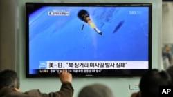图为韩国民众4月13日在首尔一个火车站观看电视画面上的朝鲜火箭发射场面