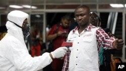 Nhân viên y tế đo thân nhiệt hành khách tại phi trường ở Lagos, Nigeria.
