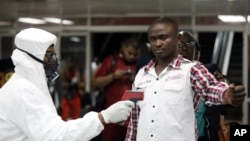 In this Aug. 6, 2014 photo, a Nigerian port health official uses a thermometer on a worker at the arrivals hall of Murtala Muhammed International Airport in Lagos, Nigeria.
