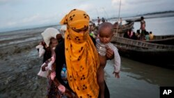 FILE - A Rohingya woman carries a child after crossing a stream on a small boat near Cox's Bazar's Dakhinpara area, Bangladesh, Sept. 21, 2017.