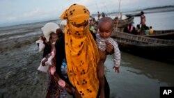 一名罗兴亚妇女带着一个小孩坐船穿过一条小河。(2017年9月21日)