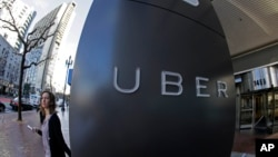 FILE- A woman leaves Uber headquarters of Uber in San Francisco, California.