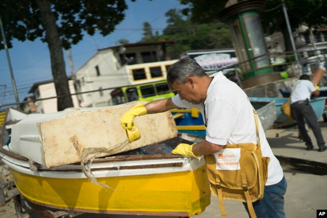 A health agent scoops water from a boat docked at Jurujuba Beach during an operation to eradicate the Aedes aegypti mosquito, in Niteroi, Brazil, March 8, 2016.