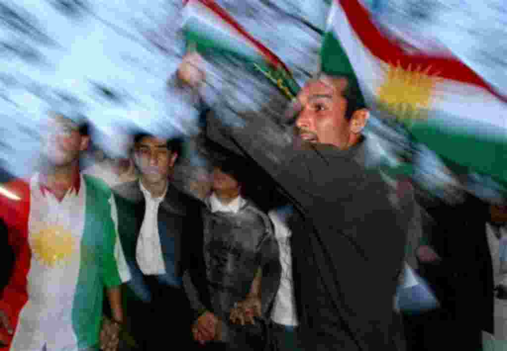 Kurdish men, one carrying the flag of Iraqi Kurdistan, celebrate the election of the new Iraqi President Jalal Talabani in Sulaimaniyah, Iraq, Wednesday, April 6, 2005. The Iraqi parliament chose Kurdish leader Talabani, reaching out to the nation's long-
