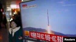Hành khách đi qua màn hình tường thuật tin tức về vụ phóng hỏa tiễn của Bắc Triều Tiên tại nhà ga ở Seoul, Hàn Quốc, ngày 7/2/2016.