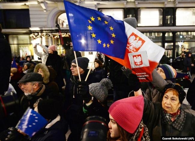 Pengunjuk rasa membawa bendera Uni Eropa pada protes anti-pemerintah di Warsawa, Polandia. Beberapa orang Polandia khawatir konflik yang berlarut-larut dengan UE mengenai anggaran dapat membuat mereka meninggalkan blok tersebut. (Foto: AP/Czarek Sokolowsk