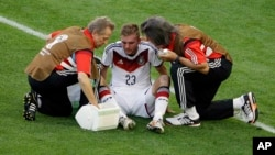 Germany's Christoph Kramer gets assistance during the World Cup final soccer match between Germany and Argentina in 2014. He was allowed to stay in the game.