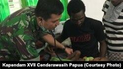 Tim dokter TNI yang dikirim ke Asmat memeriksa kondisi anak-anak yang terkena campak dan menderita kekurangan gizi.