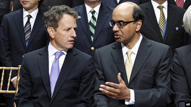 US Treasury Secretary Timothy Geithner speak with Singapore FM Tharman Shanmugaratnam, right, during the official group photo at International Monetary Fund (IMF) and World Bank Annual Meetings at IMF headquarters in Washington, September 24, 2011.
