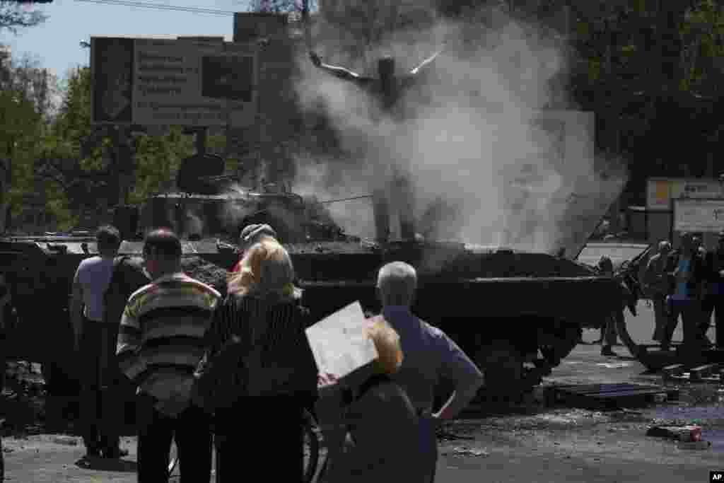 People watch as a seized armored vehicle that was set on fire smolders in the center of Mariupol, eastern Ukraine, May 10, 2014.