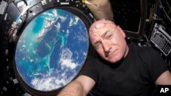 In this July 12, 2015 photo, Astronaut Scott Kelly takes a photo of himself inside the Cupola, a special module of the International Space Station that provides 360-degree viewing of the Earth and the station.