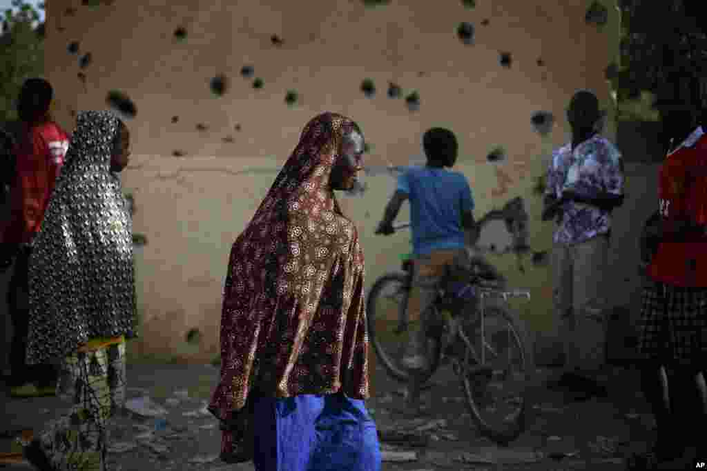 People walk through the heavily shelled police station in Gao, northern Mali, Feb. 11, 2013.