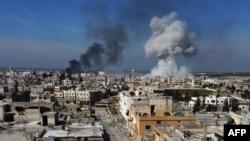 Asap mengebul di kota Saraqeb, di bagian timur provinsi Idlib di Suriah barat laut, menyusul pemboman oleh pasukan pemerintah Suriah, 27 Februari 2020.