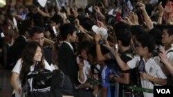 Kapten tim nasional sepakbola putri Jepang Homare Sawa (kiri) berjalan melewati penggemar yang menyambut timnya di bandara internasional Narita, Selasa (19/7).