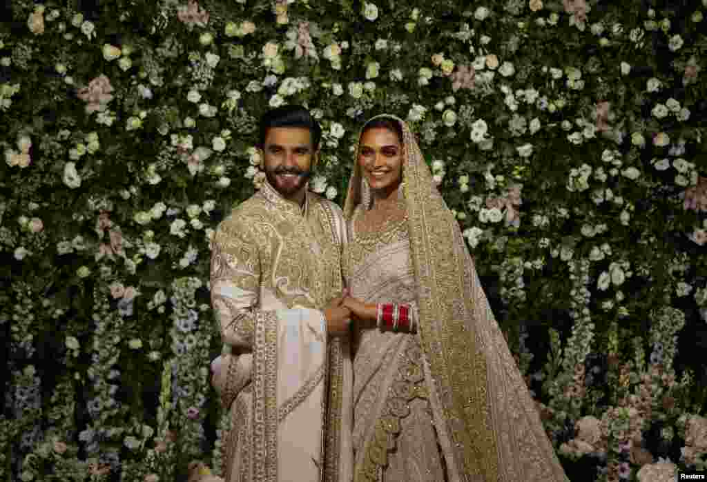 Bollywood actors Ranveer Singh and Deepika Padukone pose during a photo-op at their wedding reception in Mumbai, India.