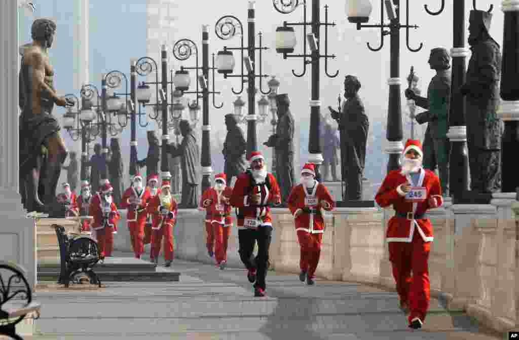 មនុស្សដែលស្លៀកពាក់ជា Santa Claus រត់កាត់ផ្លូវដែលមានសុទ្ធតែរូបចម្លាក់ ក្នុងពេលប្រកួត Santa Claus Race នៅក្នុងក្រុងស្កុបជេ (Skopje) ប្រទេសម៉ាសេដ្ឋាន (Macedonia)។
