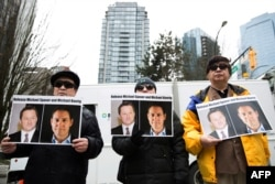 FILE - Protesters hold photos of Canadians Michael Spavor and Michael Kovrig, who are being detained by China, outside British Columbia Supreme Court, in Vancouver, March 6, 2019.