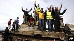 ພວກປະທ້ວງຕໍ່ຕ້ານລັດຖະບານ ຍົກມືຂຶ້ນເຮັດເປັນຮູບຕົວ V ຊຶ່ງເປັນສັນຍາລັກຂອງໄຊຊະນະ ຢູ່ເທິງລົດຖັງ ຂອງທະຫານລີເບຍ ໃກ້ໆຈະລຸລັດແຫ່ງນຶ່ງ ບ່ອນທີ່ປະຊາຊົນໂຮມຊຸມນຸມປະທ້ວງ ທີ່ເມືອງ Benghazi ຫົວເມືອງໃຫຍ່ອັນດັບ 2 ຂອງລີເບຍ (24 ກຸມພາ 2011)