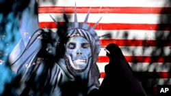 FILE - An Iranian woman walks past graffiti art characterizing the U.S. Statue of Liberty, painted on the wall of the former U.S. Embassy in Tehran, Iran, Sept. 25, 2007. An Iranian-American businessman and his father, who are serving 10-year prison sentences in Iran over their ties to the U.S., have lost a court appeal, a lawyer said Monday, Aug. 28, 2017.