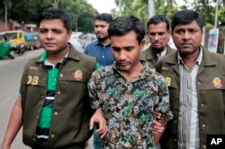 FILE - Members of Bangladesh police escort a man whom they have identified as Shariful, a member of a banned Islamic group, as they walk him in front of the media in Dhaka, Bangladesh, May 15, 2016.