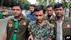 پولیس حراست میں لیے گئے ایک مشتبہ شدت پسند شریف الاسلام کو ڈھاکہ میں میڈیا کے سامنے پیش کر رہی ہے۔فائل فوٹو