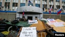 Tulisan-tulisan anti-Barat terlihat di barikade yang dipasang di luar gedung pemerintahan yang diduduki separatis pro-Rusia di Luhansk, Ukraina timur (10/4). (Reuters/Shamil Zhumatov)