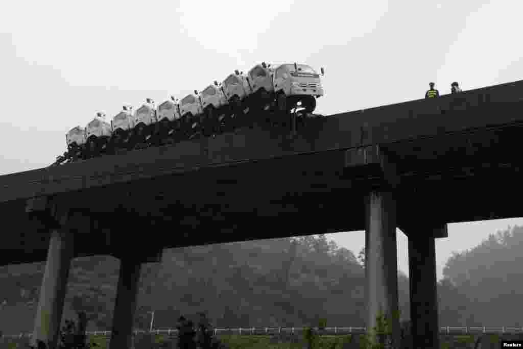 A trailer loaded with trucks hangs on the edge of the guardrail on a bridge in Kaili, Guizhou province, China, Oct. 21, 2013. According to local media, the trailer hanged on the edge of the bridge after the driver lost control of the vehicle. No injury was reported.