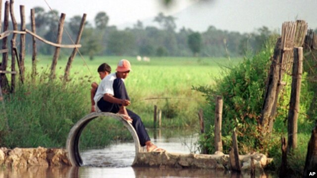 Two Cambodian boys fish on an empty drainage pipe at the natural irrigation canal in Kompong Speu province.