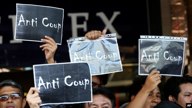 Thai anti-coup protesters hold up banners during a protest outside a shopping complex in Bangkok, Thailand Saturday, May 24, 2014.
