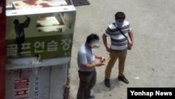 최룡해 북한 노동당 비서의 5촌 조카로 추정되는 인물(오른쪽)씨이 지난 6월 15일 서울시 관악구 한 은행 근처에서 보이스피싱 범행을 준비하고 있다.