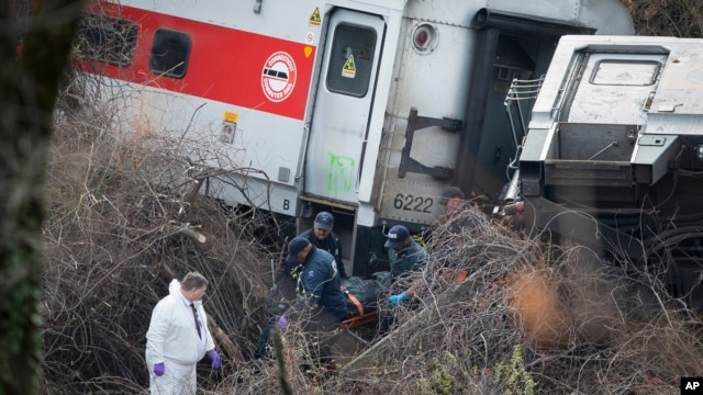 Emergency personnel remove a body from the scene of a Metro-North passenger train derailment in the Bronx borough of New York, Sunday, Dec. 1, 2013. The train derailed on a curved section of track in the Bronx on Sunday morning, coming to rest just inches