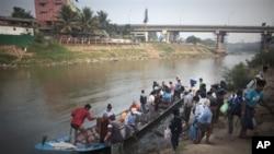 Các di dân Miến Điện và các công nhân làm việc bất hợp pháp dùng thuyền vượt sông Moei để tới Mae Sot, Thái Lan.