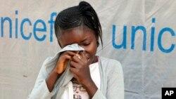 German Umba, âgée de 11 ans, est en sanglotant et se cache son visage dans sa chemise, après le décès de son père d'Ebola, à Mbandaka, RDC, 1er juin 2018.